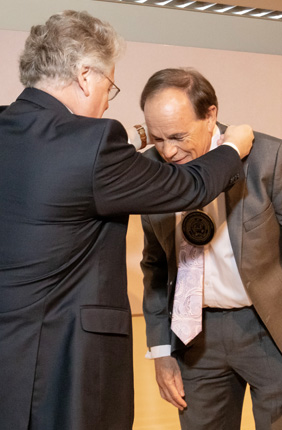 Provost Andreas Cangellaris places a medallion around the neck of Ikenberry Endowed Chair Stephen Long in recognition of his investiture.