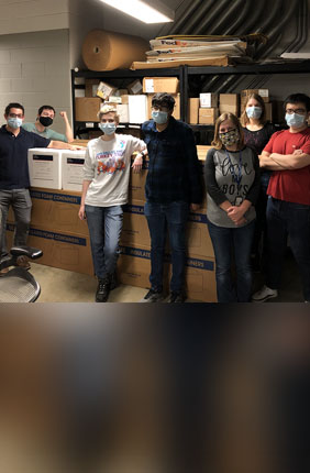 From left: Max Simon, Kyle Shelton, Laura Daigh, Auroni Gupta, Jana Radin, Katie Frye, and Xiaorui Guo stand next to a shipment of viral transfer media (VTM) prior to shipment. The group was among the almost 50 volunteers at Illinois who helped produce enough VTM for 200,000 COVID-19 tests.